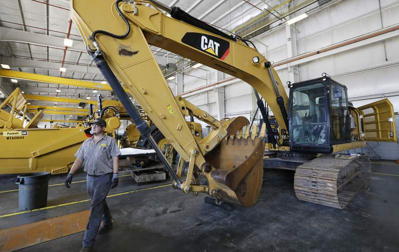 FILE - In this Sept. 18, 2019, photo a Puckett Machinery Company technician walks past a new heavy duty Caterpillar excavator that awaits modification at Puckett Machinery Company in Flowood, Miss. Caterpillar is reporting a third-quarter profit of $668 million and topped most expectations, though demand for its equipment is being driven down by the pandemic. The Deerfield, Illinois, company reported a profit Tuesday, Oct. 27, 2020, of $1.22 per share. (AP Photo/Rogelio V. Solis, File)
