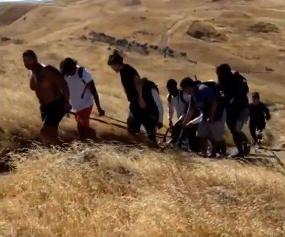 A screenshot from Cedric Lousi's viral video showing the men helping the man up the mountain.