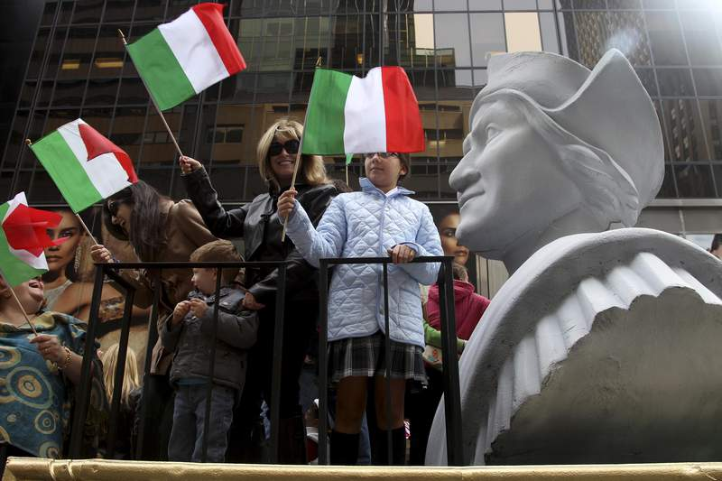 FILE - In this Oct. 8, 2012 file photo, people ride on a float with a large bust of Christopher Columbus during the Columbus Day parade in New York.  Monday, Oct. 11, 2021 federal holiday dedicated to Christopher Columbus continues to divide those who view the explorer as a representative of Italian Americans history and those horrified by an annual tribute that ignores the native people whose lives and culture were forever changed by colonialism.(AP Photo/Seth Wenig, File)
