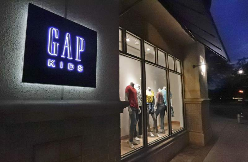 FILE - This Aug. 23, 2018, file photo shows a window display at a Gap Kids clothing store in Winter Park, Fla.  Gap is moving away from  the nations malls. The brand, which was for decades a fixture at shopping malls around the country, said that it will be closing 220 stores _ or one third of its store base  by early 2024 _ and focus on outlet malls and its e-commerce business.   (AP Photo/John Raoux, File)