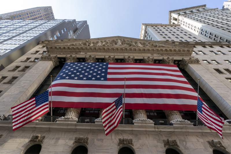 FILE - In this Monday, Sept. 21, 2020, file photo, a giant American Flag hangs on the New York Stock Exchange.  Wall Street is moving past the uncertainty of election season and, if history is a guide, investors can indeed breathe a sigh of relief. Stocks typically post solid gains following an election, no matter which party controls the White House or Congress.  (AP Photo/Mary Altaffer, File)