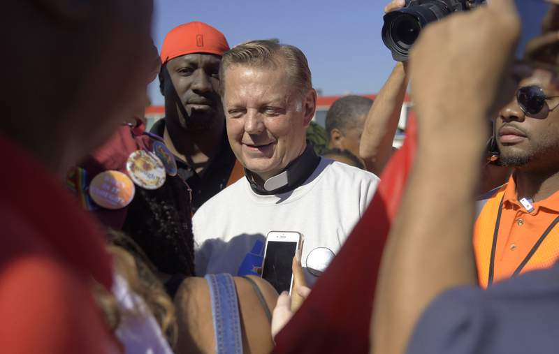 FILE - In this Saturday, July 7, 2018 file photo, The Rev. Michael Pfleger speaks to protesters before marching on the Dan Ryan Expressway in Chicago. A third man has come forward with allegations that Rev. Pfleger made an unwanted sexual advance against him as a teenager, following two brothers' allegations that the priest abused them decades ago when they were teens. (AP Photo/Annie Rice, File)