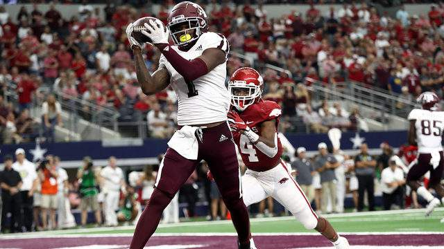 Quartney Davis #1 of the Texas A&M Aggies makes a touchdown pass reception against Jarques McClellion #4 of the Arkansas Razorbacks in the fourth quarter during the Southwest Classic at AT&T Stadium on September 28, 2019 in Arlington, Texas.