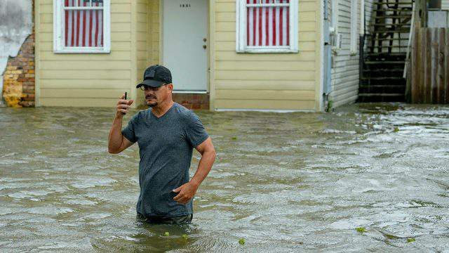 Barry Williams talks to a friend on his smartphone on Saturday, July 13, as he wades through storm surge from Lake Pontchartrain in Mandeville, Louisiana.