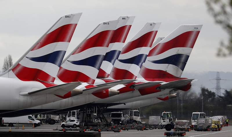 FILE - In this Wednesday, March 18, 2020 file photo, British Airways planes parked at Terminal 5 Heathrow airport in London. British Airways parent company said Thursday, Sept. 10, 2020 it is to cut flights due to coronavirus travel restrictions and quarantine requirements and confirmed that it is raising 2.7 billion euros ($3.2 billion) through the sale of new shares. (AP Photo/Frank Augstein, File)