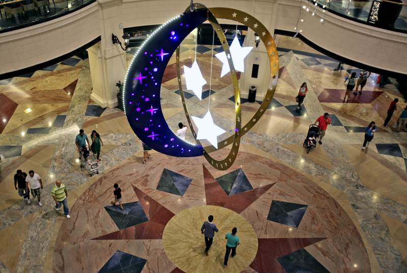FILE - In this Saturday, June 28, 2014, file photo, people walk inside a shopping mall with Ramadan decorations as they prepare for the holy month of Ramadan in Dubai, United Arab Emirates. As the holy Muslim fasting month of Ramadan approached, Dubai is parting with a longstanding requirement that restaurants must be covered by curtains during sunlight hours. (AP Photo/Kamran Jebreili, File)