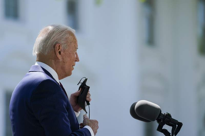 President Joe Biden removes his face mask to speak about COVID-19, on the North Lawn of the White House, Tuesday, April 27, 2021, in Washington. (AP Photo/Evan Vucci)