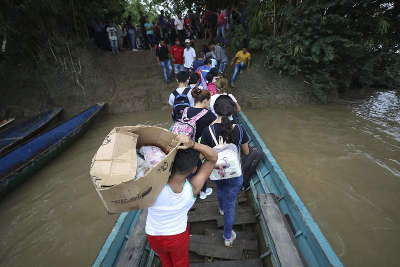 FILE - In this March 26, 2021 file photo, Venezuelans disembark a boat on the Arauca River, the natural border between Venezuela and Colombia, as they flee to Arauquita, Colombia, and seek shelter following clashes between Venezuela's military and a Colombian armed group.  According to the international monitoring group, Human Rights Watch, on Monday, April 26, 2021, Venezuelan security forces operating against Colombian rebels along the border have executed peasants, tortured and arbitrarily arrested people, and prosecuted civilians in military courts, prompting roughly 6,000 people to flee. (AP Photo/Fernando Vergara, File)