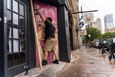 Workers board up bars on Sixth Street in Austin after Gov. Greg Abbott closed them in Texas for the second time in three months Friday during the COVID-19 pandemic. (Jordan Vonderhaar for The Texas Tribune)
