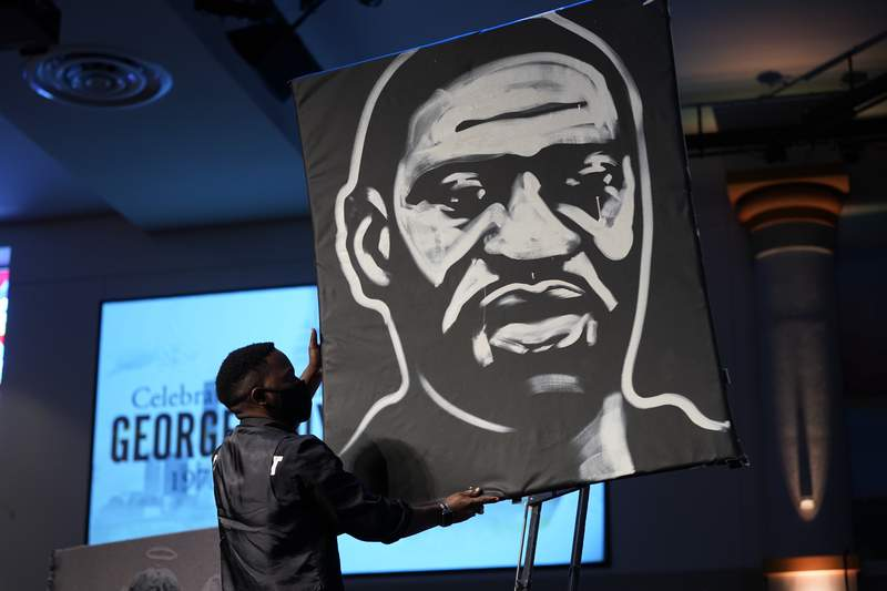 FILE - In this June 9, 2020, file photo a man draws an image of George Floyd during the funeral service for Floyd at The Fountain of Praise church in Houston. Americans' suggestions of suitable statuesfor President Donald Trump's planned National Garden of American Heroes are in, and they look considerably different from the predominantly white worthies that the administration has locked in for many of the pedestals. Lehigh County, Pennsylvania Commissioner Amy Zanelli, suggested George Floyd, Breonna Taylor, and other Black Americans whose killings by police sparked massive street protests. (AP Photo/David J. Phillip, Pool, File)