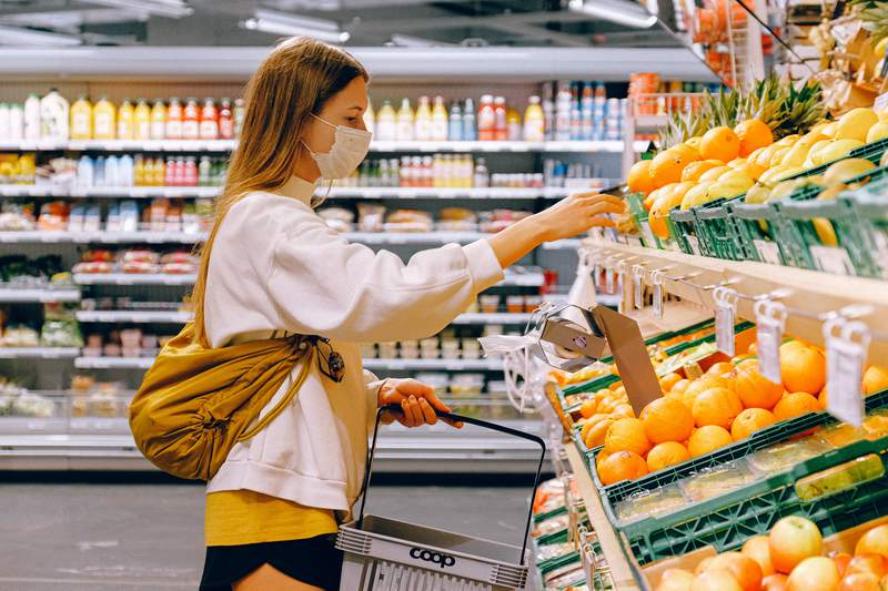 Woman buying food at grocery store.