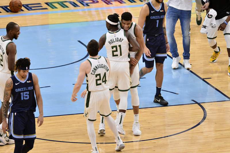 Milwaukee Bucks forward Giannis Antetokounmpo, center right, reacts after Bucks guard Jrue Holiday (21) scored the winning basket in the second half of an NBA basketball game against the Memphis Grizzlies, Thursday, March 4, 2021, in Memphis, Tenn. (AP Photo/Brandon Dill)