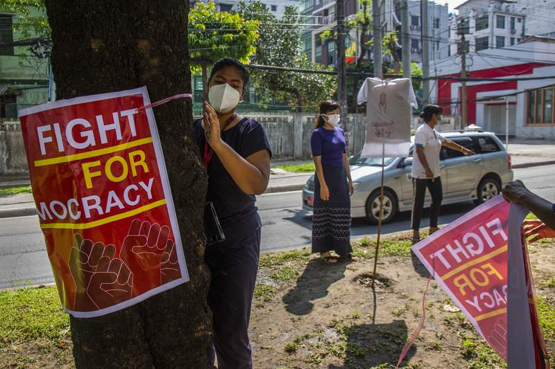 Anti-coup protesters place posters of slogans on trees along a road during a demonstration at Yangon, Myanmar on Wednesday, April 21, 2021. Aid workers and activists are warning Myanmar's political upheavals risk causing a regional refugee crisis as the strife following a February coup displaces growing numbers of people who have lost their livelihoods. (AP Photo)