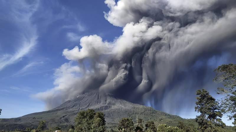 """Mount Sinabung spews volcanic materials during an eruption, in Karo, North Sumatra, Indonesia, Sunday, Aug. 23, 2020. Sinabung is among more than 120 active volcanoes in Indonesia, which is prone to seismic upheaval due to its location on the Pacific """"Ring of Fire,"""" an arc of volcanoes and fault lines encircling the Pacific Basin. (AP Photo)"""
