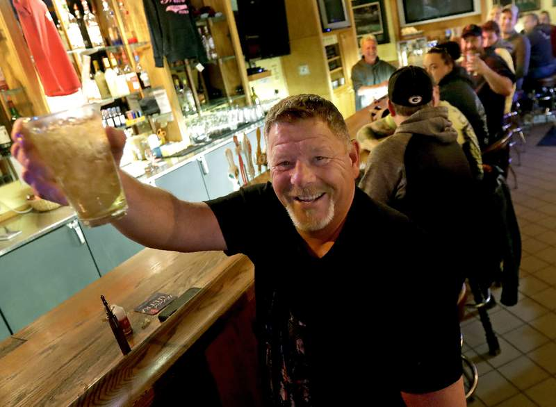 Marvin Radtke toasts the opening of the Friends and Neighbors bar following the Wisconsin Supreme Court's decision to strike down Gov. Tony Evers' safer-at-home order amid the coronavirus pandemic, Wednesday, May 13, 2020, in Appleton, Wis. (William Glasheen/The Post-Crescent via AP)