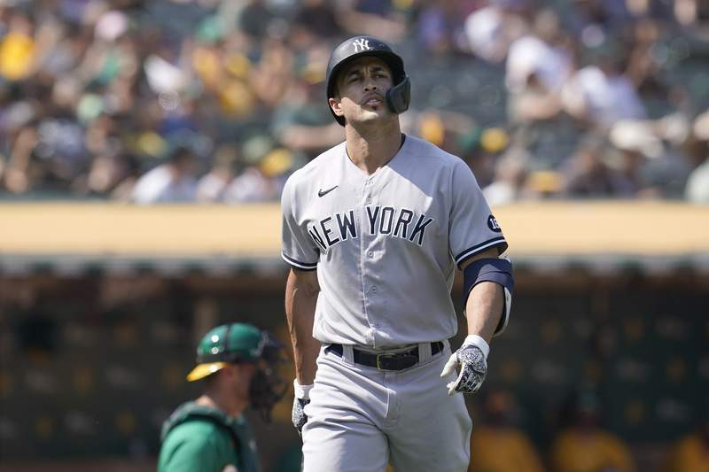 New York Yankees' Giancarlo Stanton walks to the dugout after striking out against the Oakland Athletics during the seventh inning of a baseball game in Oakland, Calif., Saturday, Aug. 28, 2021. (AP Photo/Jeff Chiu)