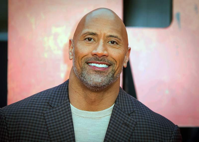 """FILE - In this April 11, 2018, file photo, actor Dwayne Johnson poses for photographers at the premiere of the """"Rampage,"""" in London. Johnson will host and Justin Bieber, Miley Cyrus and Jennifer Hudson will perform on a globally broadcast concert calling on world leaders to make coronavirus tests and treatment available and equitable for all. The advocacy organization Global Citizen and the European Commission announced Monday, June 22, 2020 that Global Goal: Unite for Our Future  The Concert will air on June 27. (Photo by Vianney Le Caer/Invision/AP, File)"""