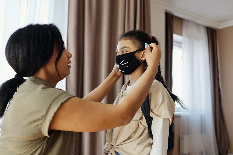 A woman puts a mask on a child.