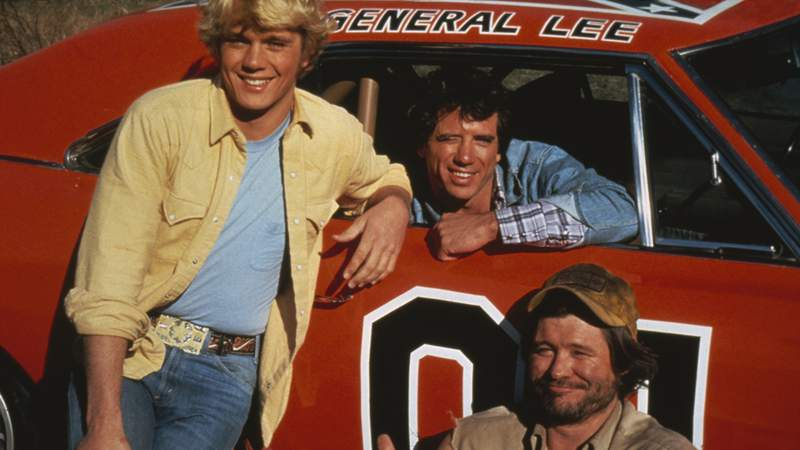 American actors (left to right) John Schneider, Tom Wopat and Ben Jones as Bo Duke, Luke Duke and Cooter, respectively,  in the TV series 'The Dukes of Hazzard', circa 1983. They are posing with the General Lee, a 1969 Dodge Charger prominently featured in the series. (Photo by Fotos International/Hulton Archive/Getty Images)