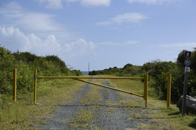 FILE - In this Jan. 13, 2017 file photo, a gate stands closed near Ferro Port lighthouse at Verdiales Key point on the south coast of Vieques island, Puerto Rico. The reopening of hiking trails and various white-sand beaches on two tiny Puerto Rican islands long used as Navy bombing ranges and now popular with tourists will be delayed more than a decade, according to a federal report released Friday, March 26, 2021. (AP Photo/Carlos Giusti, File)