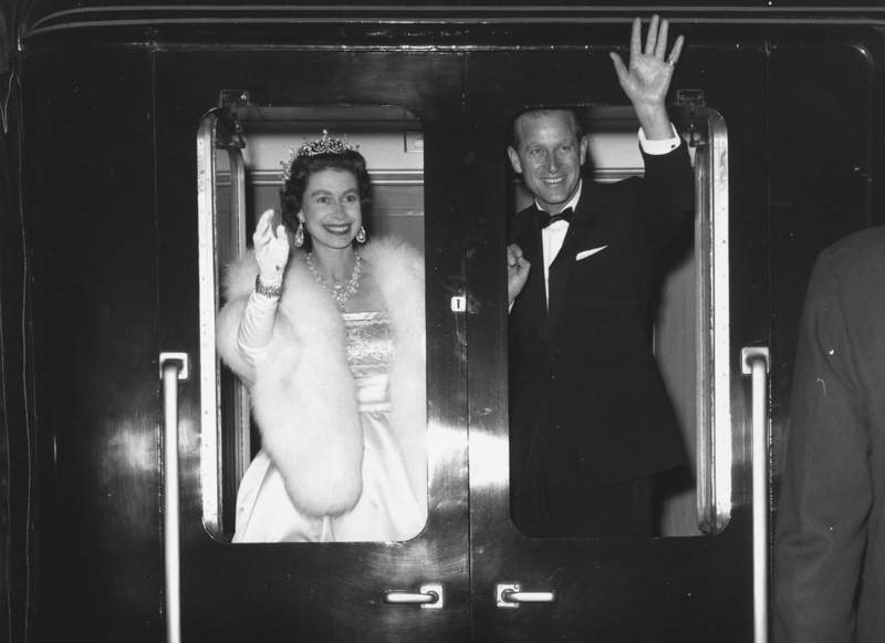 """Queen Elizabeth II and Prince Philip, the Duke of Edinburgh, wave as they leave Liverpool after attending an ice show, """"Snow White And The Seven Dwarfs"""" on May 25, 1961."""