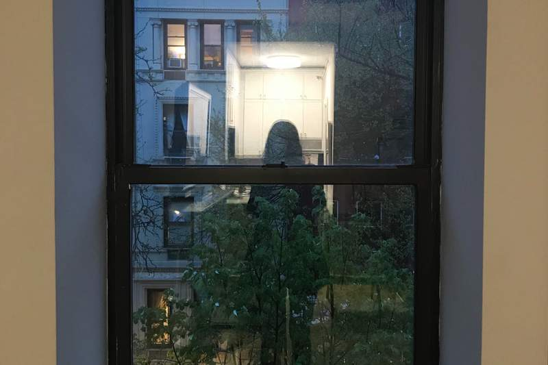 In this April 26, 2020, photo, Sarah DiLorenzos reflection can be seen as she takes a picture out of the window of her apartment in New York. Everyone is struggling during the coronavirus pandemic. But most are struggling with too much. Those who live alone are struggling with less. (AP Photo/Sarah DiLorenzo)