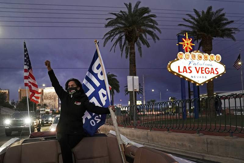 FILE - In this Nov. 7, 2020, file photo, Socorro Ulloa, a supporter of then-President-elect Joe Biden and Vice President-elect Kamala Harris, carries flags while riding in the back of a limousine in Las Vegas. Nevada lawmakers have passed a bill aiming to make the state the first to weigh in on the 2024 presidential primary contests. The move on Sunday, May 30, 2021, upends decades of political tradition and is likely to prompt pushback from other early states that want to retain their places in the calendar. Nevada's bill still needs to be approved by Democratic Gov. Steve Sisolak to become law, and it also requires the backing of the national parties to make the change for the 2024 calendar. (AP Photo/Jae C. Hong, File)