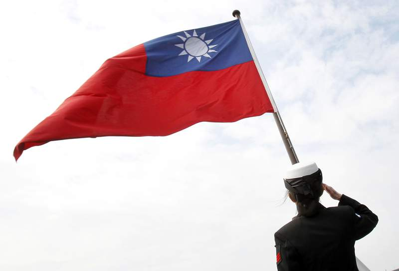 FILE - In this Jan. 31, 2018, file photo, a Taiwanese military officer salutes to Taiwan's flag onboard Navy's 124th fleet Lafayette frigate during military exercises off Kaohsiung, southern of Taiwan. China and Taiwan traded accusations Monday, Oct. 19, 2020, over a violent altercation that broke out between Chinese diplomats and Taiwan government employees at a recent Taiwan National Day reception in Fiji.  (AP Photo/Chiang Ying-ying, File)