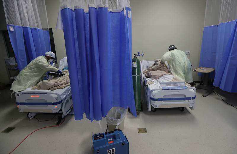 Medical personnel watch over COVID-19 patients at DHR Health, Wednesday, July 29, 2020, in McAllen, Texas. At DHR Health, the largest hospital on the border, roughly half of the 500 beds belong to coronavirus patients isolated in two units. A third unit is in the works. (AP Photo/Eric Gay)