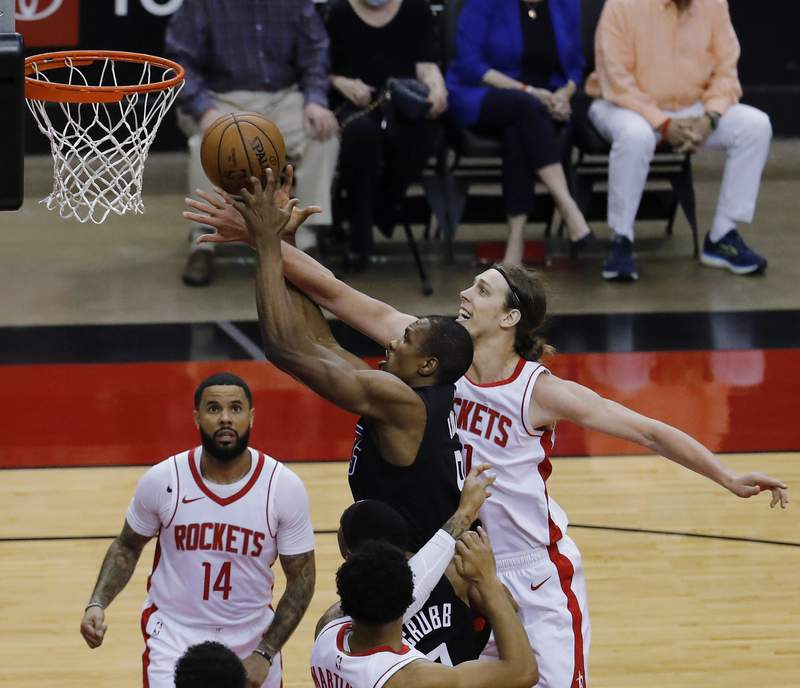 Los Angeles Clippers' Serge Ibaka (9) drives to the basket as Houston Rockets' Kelly Olynyk (41) defends during the first quarter of an NBA basketball game Friday, May 14, 2021, in Houston. (Bob Levey/Pool Photo via AP)