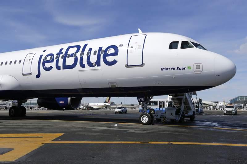 FILE- This March 16, 2017, file photo, shows a JetBlue airplane at John F. Kennedy International Airport in New York. JetBlue Airways is considering whether to keep its headquarters in New York or move to Florida. The airline has been based in the Queens neighborhood of Long Island City since it started flying in 2000. (AP Photo/Seth Wenig, File)