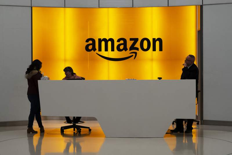 FILE - In this Feb. 14, 2019 file photo, people stand in the lobby for Amazon offices in New York.  Amazon is jumping into the podcast-making business. The online shopping giant said it plans to buy Wondery, a 4-year-old producer of popular true crime podcasts such as Dr. Death and Dirty John.   (AP Photo/Mark Lennihan, File)