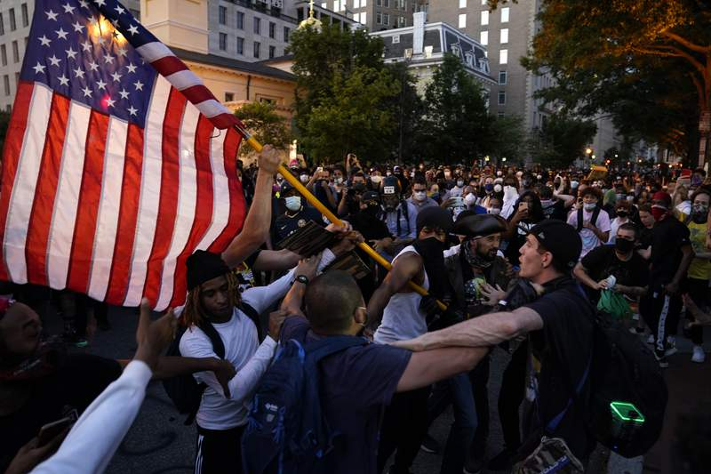 Demonstrators clash as people gather to protest the death of George Floyd, Saturday, May 30, 2020, near the White House in Washington.  Protest erupted across the United States to protest the death of  Floyd, a black man who was killed in police custody in Minneapolis on May 25.. (AP Photo/Evan Vucci)