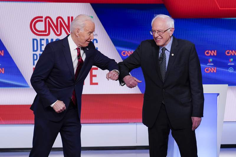 FILE - In this March 15, 2020 file photo, now Democratic presidential candidate former Vice President Joe Biden, left, and Sen. Bernie Sanders, I-Vt., right, greet one another before they participate in a Democratic presidential primary debate at CNN Studios in Washington. Former staffers from Bernie Sanders presidential campaign want to harness strong support for the Vermont senator among Hispanics to bolster Joe Biden in two battleground states that could prove critical in Novembers election. Nuestro PAC is launching a 30-second spot that will begin airing Thursday for two weeks in heavily Hispanic Nevada and Iowa. (AP Photo/Evan Vucci)