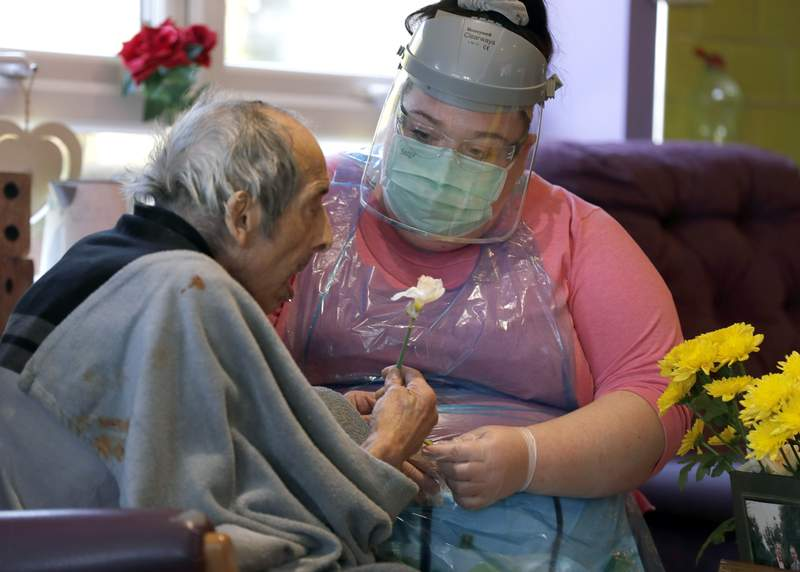 In this April 20, 2020, photo, a nurse sits beside a resident in the red zone where those sick with coronavirus stay at Wren Hall nursing home in the central England village of Selston. The coronavirus pandemic is taking a huge emotional and physical toll on staff in Britains nursing homes, who often feel like they're toiling on a forgotten front line. (AP Photo/Frank Augstein)