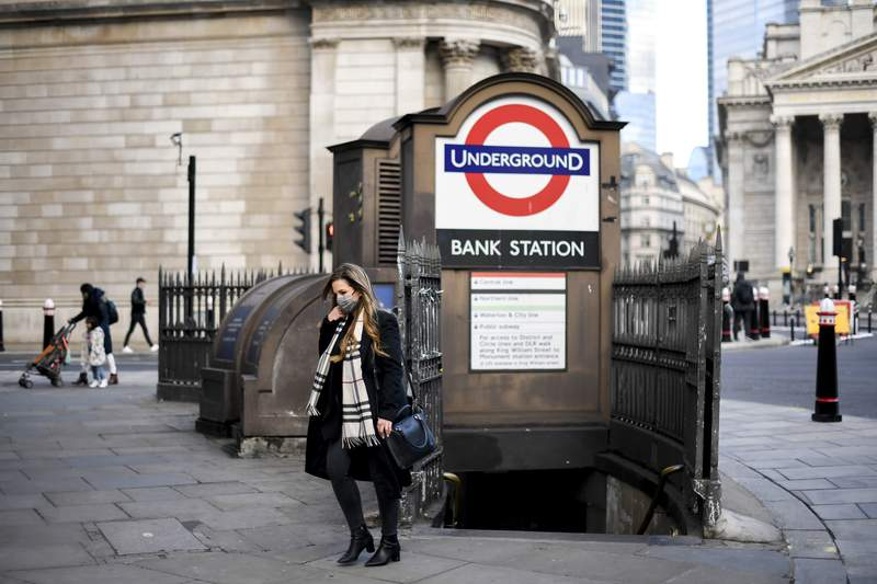 A woman wears a face mask as she steps out of Bank underground station, in London, Tuesday, Dec. 8, 2020.  The United Kingdom is beginning a mass vaccination campaign to inoculate the population against COVID-19 virus, with the elderly, vulnerable and key workers among the first to receive the first part of the inoculation.  (AP Photo/Alberto Pezzali)