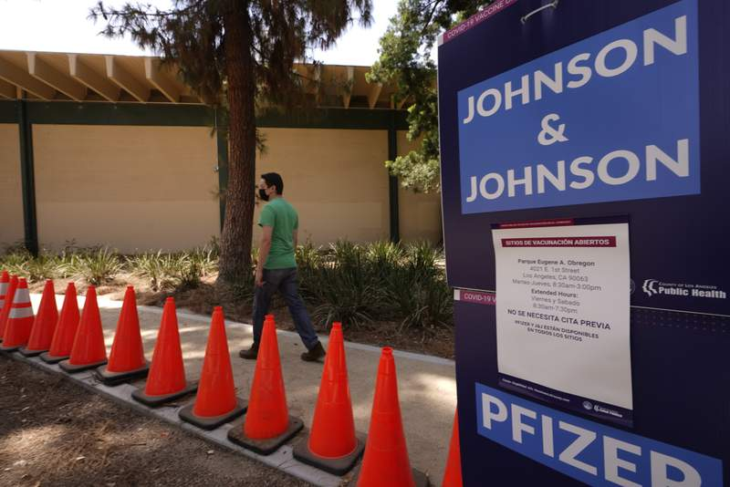 Carlos Arrendondo arrives for his appointment to get vaccinated, as banners advertise the availability of the Johnson & Johnson and Pfizer COVID-19 vaccines at a county-run vaccination site at the Eugene A. Obregon Park in Los Angeles Thursday, July 22, 2021. The top health official in Los Angeles County on Thursday implored residents to get vaccinated as the region experiences a coronavirus surge similar to last summer's.  (AP Photo/Damian Dovarganes)