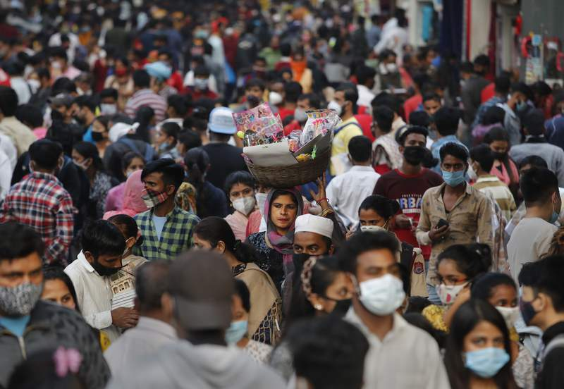 A woman without a mask walks in a crowded market selling toys in New Delhi, India, Thursday, Nov. 12, 2020. Authorities in New Delhi have banned firecrackers and are appealing to people to celebrate the Hindu festival of lights at home. Coronavirus infections have been rising in the capital and authorities are worried large festival crowds will worsen the virus situation. (AP Photo/Manish Swarup)
