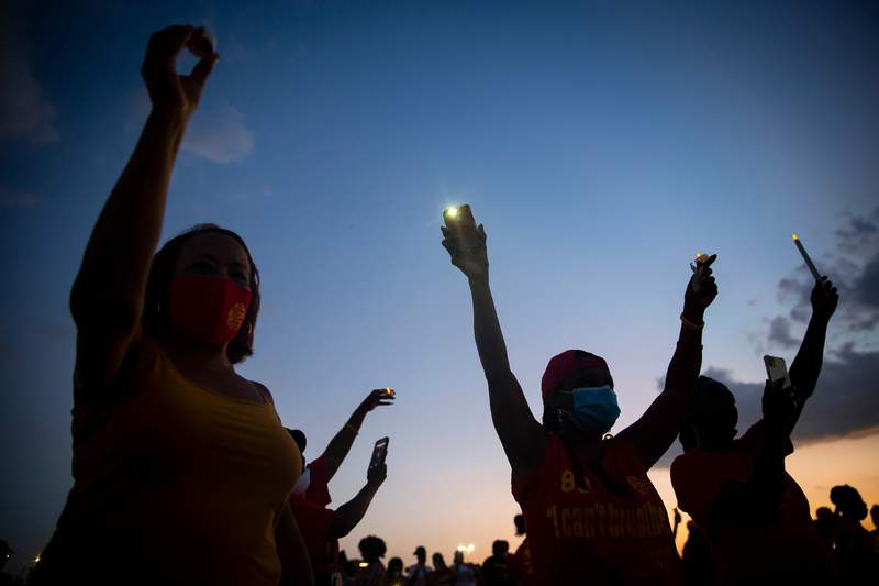 Candles are held up in the air during a vigil for George Floyd at Yates High School in Houston on June 8, 2020.