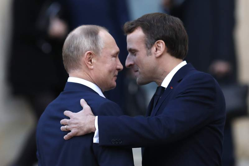 FILE - In this Monday, Dec. 9, 2019 file photo, French President Emmanuel Macron, right, welcomes Russian President Vladimir Putin wave at the Elysee Palace in Paris, France. Spring is not turning out the way Russian President Vladimir Putin might have planned it. A nationwide vote on April 22, 2020 was supposed to finalize sweeping constitutional reforms that would allow him to stay in power until 2036, if he wished. But after the coronavirus spread in Russia, that plebiscite had to be postponed  an action so abrupt that billboards promoting it already had been erected in Moscow and other big cities. (AP Photo/Thibault Camus, File)
