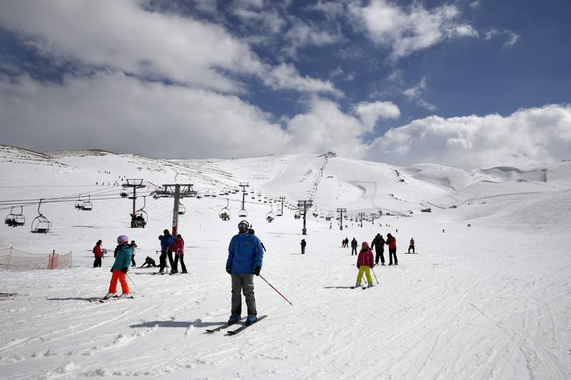 FILE - In this Friday, Feb. 22, 2019 file photo, people ride ski lifts as other skiers slide down the hill on a sunny day at the Faraya-Mzaar ski resort, in Faraya, northeast of Beirut, Lebanon. As several countries have suspended access to the ski slopes to stop the spread of the coronavirus pandemic, the World Health Organizations emergencies chief said the risk of catching COVID-19 while skiing is likely minimal. I suspect many people wont be infected barreling down the slopes on their skis, said Dr. Michael Ryan at a WHO news briefing on Monday, Nov, 30, 2020. (AP Photo/Bilal Hussein, file)