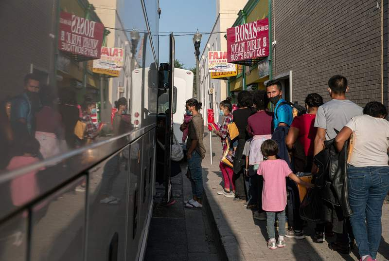 A group of migrants wait to board a charter bus in front of the Catholic Charities RGV Humanitarian Respite Center in McAllen on July 27, 2021.