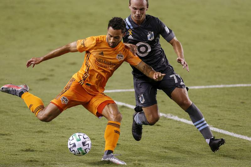 HOUSTON, TEXAS - SEPTEMBER 02: Niko Hansen #12 of Houston Dynamo shoots the ball while defended by Chase Gasper #77 of Minnesota United in the second half at BBVA Compass Stadium on September 02, 2020 in Houston, Texas. (Photo by Tim Warner/Getty Images)