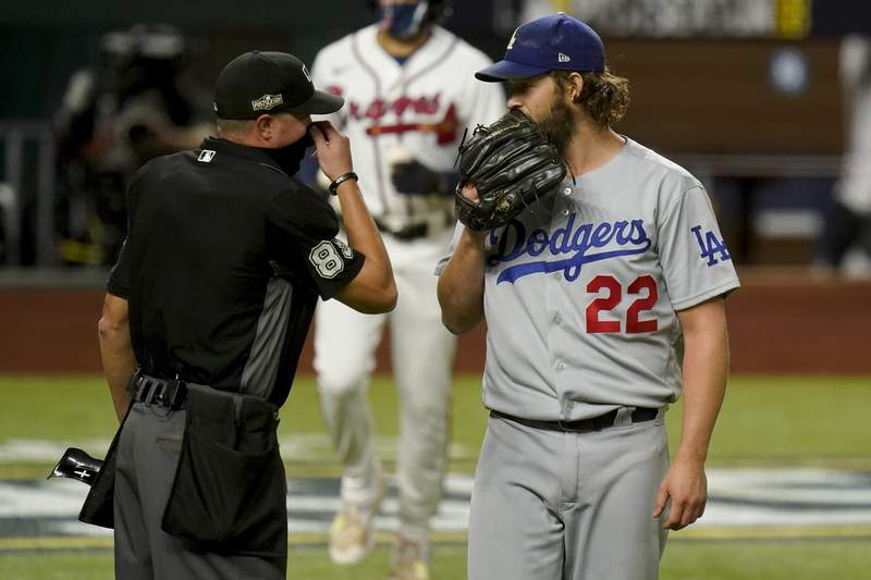 Los Angeles Dodgers starting pitcher Clayton Kershaw talks with home plate umpire Cory Blaser during the first inning in Game 4 of a baseball National League Championship Series against the Atlanta Braves Thursday, Oct. 15, 2020, in Arlington, Texas. (AP Photo/Eric Gay)