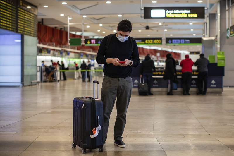 A passenger wears a protective mask at Adolfo Suarez-Barajas international airport on the outskirts of Madrid, Spain, Wednesday, March 11, 2020. Spanish authorities closed schools and halted direct flights to and from Italy. Italy is the country with most coronavirus cases in Europe, and Spain this week reported a sharp increase in cases. For most people, the new coronavirus causes only mild or moderate symptoms, such as fever and cough. For some, especially older adults and people with existing health problems, it can cause more severe illness, including pneumonia. (AP Photo/Bernat Armangue)