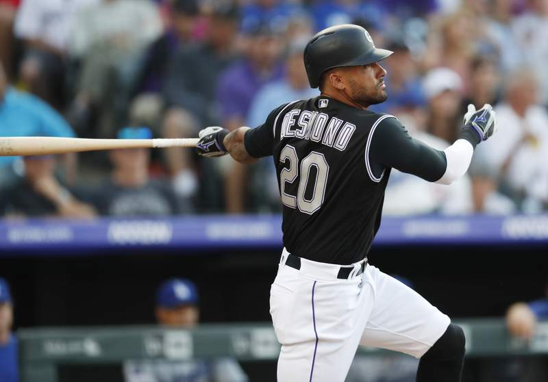 FILE - In this July 29, 2019, file photo, Colorado Rockies' Ian Desmond follows the flight of his triple off Los Angeles Dodgers starting pitcher Kenta Maeda in the second inning of a baseball game in Denver. Desmond plans to sit out this season to be with his family and help the youth baseball program in his hometown in Florida. The 34-year-old Desmond wrote on Instagram that the COVID-19 pandemic has made this baseball season one that is a risk I am not comfortable taking. (AP Photo/David Zalubowski, File)