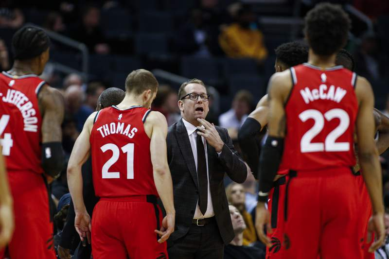 FILE - In this Jan. 8, 2020, file photo, Toronto Raptors coach Nick Nurse, center, gathers his team during a timeout in the first half of an NBA basketball game against the Charlotte Hornets in Charlotte, N.C. The Raptors have an NBA championship to defend, a very long stay at the Disney complex awaiting them and plenty of unanswered questions on how the restart of the season will work. As the NBAs lone Canadian team, theres an added complexity: The U.S. border. Nurse said Tuesday, June 9, 2020, that his team is still working through various scenarios for having workouts before heading to Disney World near Orlando, Florida along with 21 other teams next month for the restart of the season. (AP Photo/Nell Redmond, File)
