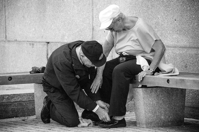 A man ties a woman's shoes for her.