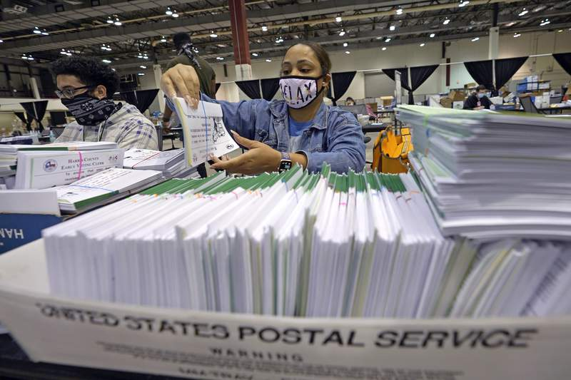 Harris County election worker Romanique Tillman prepares mail-in ballots to be sent out to voters Tuesday, Sept. 29, 2020, in Houston. Texas is one of just a handful of states that declined to expand absentee voting this year because of the the coronavirus pandemic. (AP Photo/David J. Phillip)