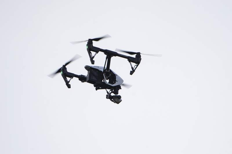 FILE - In this Thursday, Aug. 8, 2019, file photo, a drone flies in a residential neighborhood in Upper Moreland, Pa. Federal officials are outlining new rules that will let operators fly small drones over people and at night. (AP Photo/Matt Rourke, File)